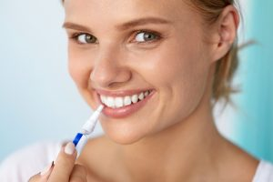 Healthy White Teeth. Closeup Portrait Of Beautiful Happy Smiling Woman With Perfect White Smile Holding Teeth Whitening Pen. Dental Beauty And Health, Tooth Care Concept. High Resolution Image